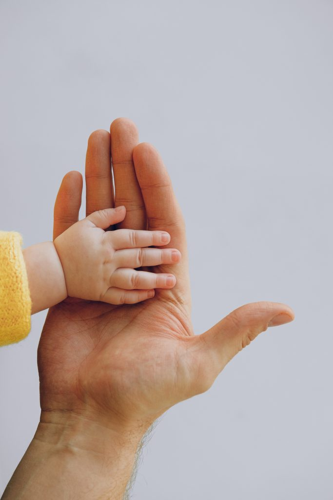 Adult hand and child's hand